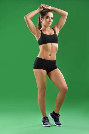 female sexuality: Beautiful sportswoman posing on green background Stock Photo