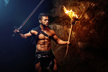 Fearless young muscular warrior with a torch in the dark