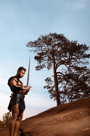 militaire sexy: Jeune guerrier musclé avec une épée à la montagne