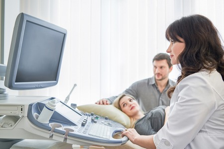 Loving couple attending doctor for pregnancy ultra sound procedu