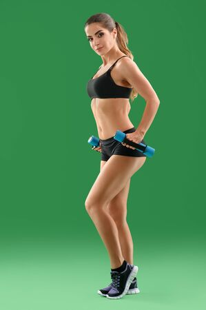 sexualidad: Young attractive woman with dumbbells in her hands posing in stu