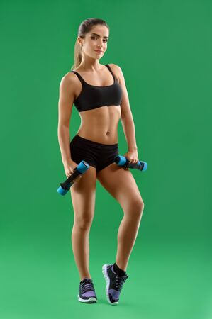 Young attractive woman with dumbbells in her hands posing in stu