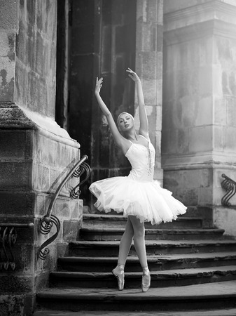 Young ballerina woman posing on stairs