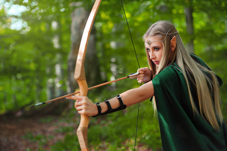 female sexuality: Beautiful female elf archer in the forest hunting with a bow Stock Photo