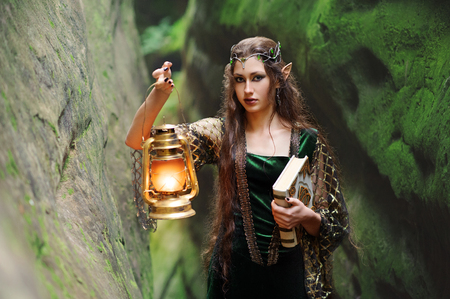 Young beautiful female elf walking through the forest with a boo