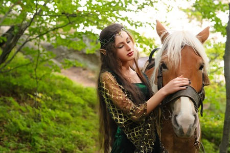 female sexuality: Female elf in the forest with her horse Stock Photo