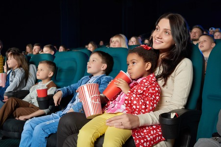 crowd happy people: Children with parents enjoying a movie together at the cinema