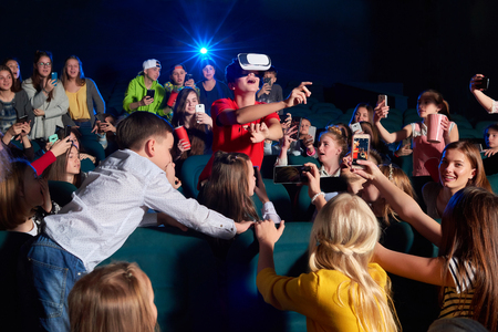 movie film: Young boy wearing virtual reality glasses at the cinema Stock Photo