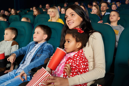 Children with parents enjoying a movie together at the cinema
