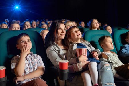 映画館で一緒に映画を楽しんでいる親を持つ子供