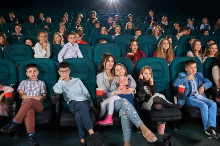 movie film: Children with parents enjoying a movie together at the cinema