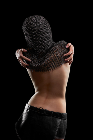 Rearview studio shot of a naked woman in a chain mail posing seductively touching herself sensually femininity sensuality seduction erotic embracing hugging concept.