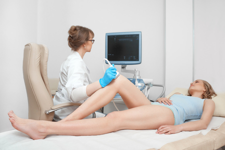 Woman getting knee ultrasound scanning examination at the clinic