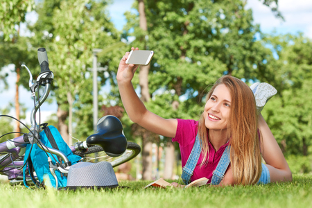 caller: Young woman using her smart phone at the park