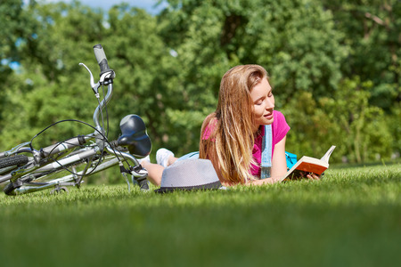 turismo ecologico: Young woman reading a book after cycling at the local park