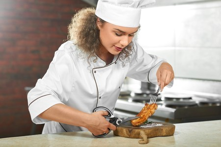 Professional chef cutting chicken steak with scissors Stock Photo - 84807614