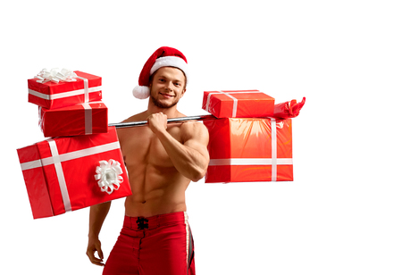 Ripped Santa holding a barbell with presents Stock Photo