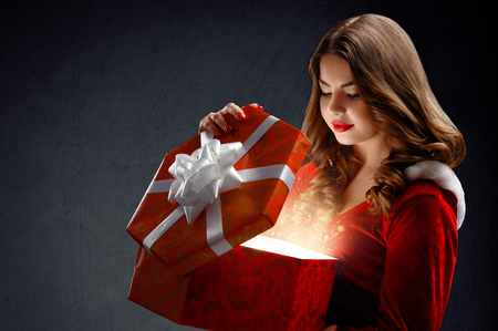 sexy young woman in red suit of Santa Claus  with gifts. On a da
