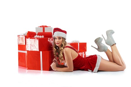 Gorgeous female in Christmas outfit lying near the pile of prese Stock Photo