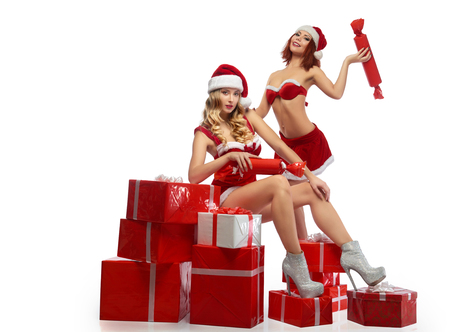 Two Christmas girls posing with a pile of presents