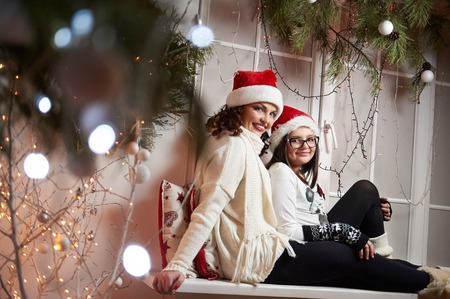 Happy mother and daughter sitting on a windowsill on Christmas e