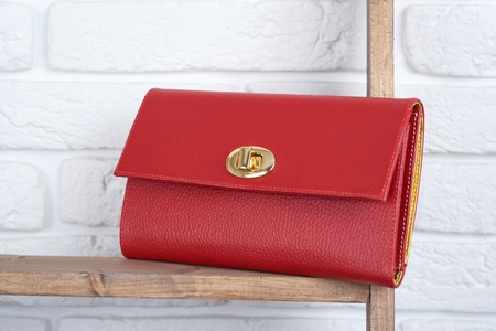 Red woman s leather clutch on the white wall background