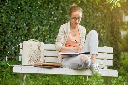 Young student writes on the park s bench Stock Photo