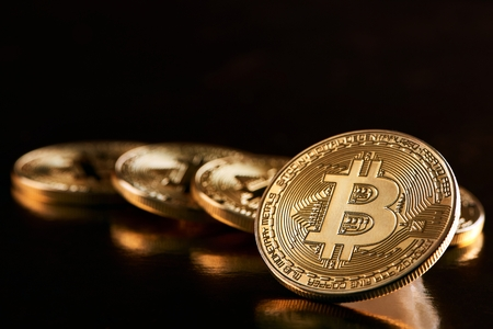 One golden bitcoin as main cryptocurrency in front of other golden bitcoins isolated on balck background Stock Photo