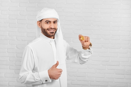 Smiling Arabian man keeps bitcoin and looks very happy. He wears traditional white Arabian costume,golden watch and cufflinks. A businessman looks very positive and happy.