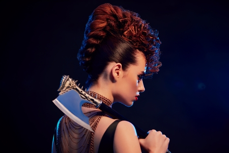 Back view of young beatiful warrior girl keeping sharp metallic axe with thorns. Model wears bright original make up and fashionable, stylish hairdress. Golden chains with crosses on neck. Stock Photo