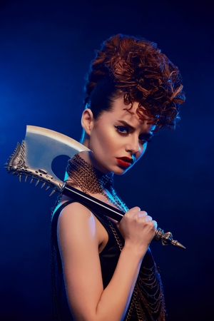 Close up of dangerous beatiful girl keeping sharp metallic axe with thorns. Model wears black top with opened shoulders,bright make up and stylish hairdress. She stands on dark blue smoky background.