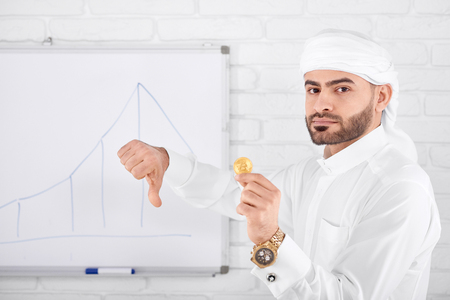 Attractive rich muslim male model in traditional Islamic clothing being serious and holding golden bitcoin and showing thumbs down. Horizontal shot. Financial problems, cryptocurrency, digital money.