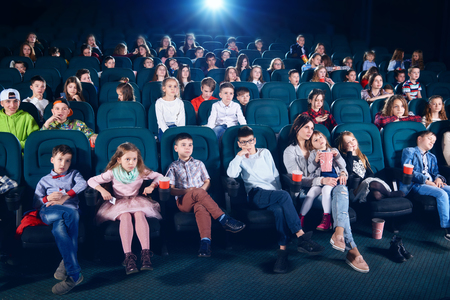 Frontview of people sitting in the cinema hall. Boys and girls watching interesting movie and looking very emotional, frightened and exited. Children wear colorful trendy clothes.