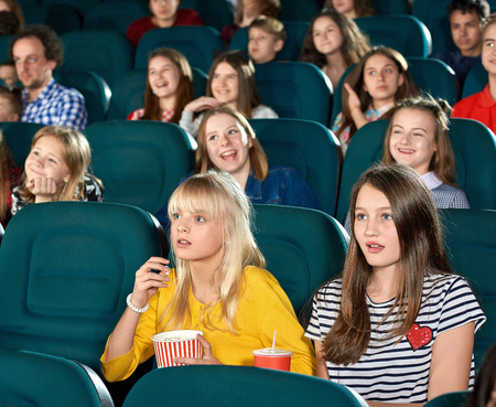 Exited girls watching movie in the cinema. Children ooking very interested, drinking fizzy drinks, sitting on other childrens background. They wearing trendy colorful clothes. looking frightened.