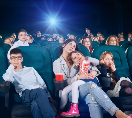 Pretty senior sister is watching movie or cartoon in the new cinema hall with junior children . children looking very interested and exited. There are other people on the backgroung.