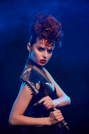 Side view of fantastic girl keeping sharp metallic axe with thorns. Female warrior standing on dark blue smoky background. Model wearing black top with opened shoulders, make up and stylish hairdress.