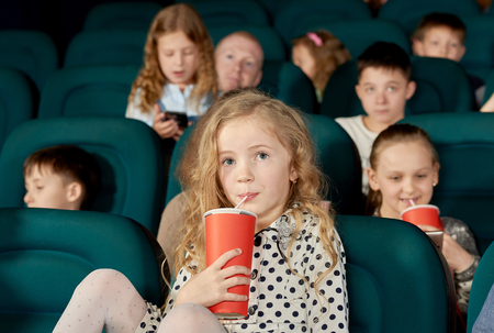 Pretty girl with blonde curly hair drinking fizzy drink in cinema. Kid wearing white dotted dress with white tights. There are many little children watching movie on background. 版權商用圖片