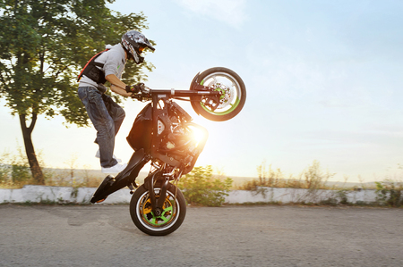 Ivano-Frankivsk, Ukraine - 28 August 2015 : colorful sideview of extreme impressing stunt driver is jumping on his sport motorcycle while riding in extreme way. Summer sunny evening.