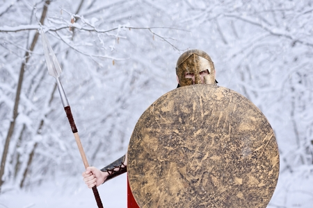 Spartan warrior wearing red long cape is looking in camera standing in white dense winter forest. He has metallic spear, shield and helmet on head. All trees covered with snow. Its cold, frosty.