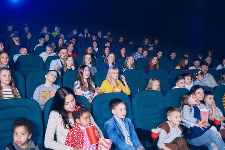 frontview of young exited people watching interesting movie in cinema hall. Boys and girls look very emotional and happy. Models wearing colorful clothes,eating popcorn, drinking fizzy drinks.