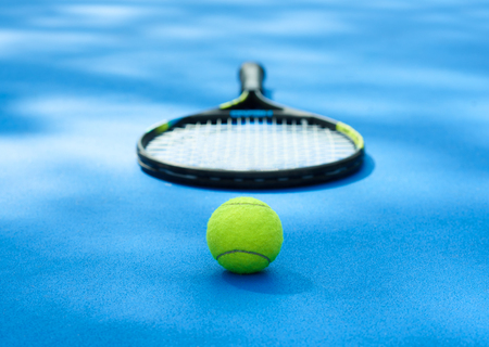 Yellow tennis ball is laying near professional racket on blue cort carpet. Made for playing tennis. Contrast image with satureted colors and shadows. Concept of sport equipment photo.