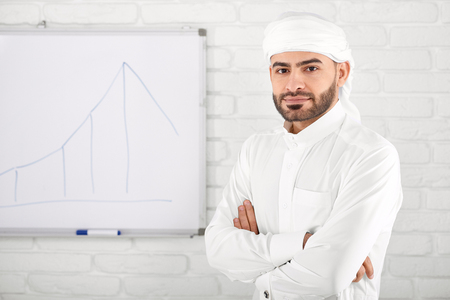Handsome young muslim male in traditional Islamic clothing standing in front of financial chart painted on white board. Concept of cryptocurrency and digital money, mining, web banking. Reklamní fotografie
