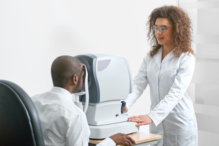 Backview of young smiling man, wearing white shirt and looking in apparatus during vision checking. Ophthalmologist is using special medical equipment for eye health saving and improving.