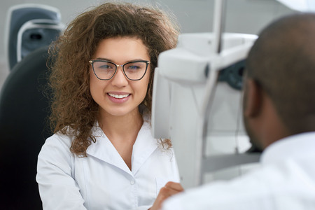 Backview of young man, wearing white shirt and looking in apparatus during vision checking. Smiling, friendly ophthalmologist is using special medical equipment for eye health saving and improving. Stock Photo