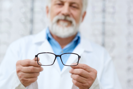 Expirienced doctor advising eyeglasses in ophthalmologic cabinet. Professinal oculist with high skills. Good doctor helping patient.