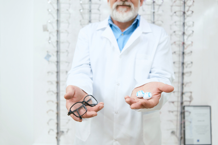 Oculist advising to try the eyeglasses on. expirienced, skilled oculist. Kind professinal helping patients improving vision, be healthy. Stock Photo