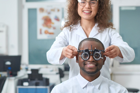 Frontview of young smiling man, wearing white shirt and looking at camera through during vision checking. Ophthalmologist is using special medical equipment for eye health saving and improving.