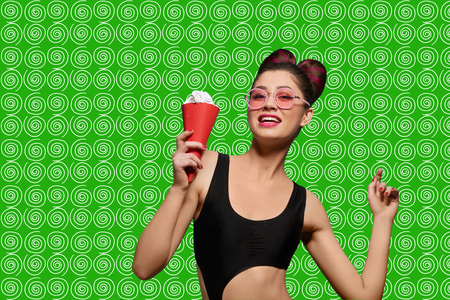 Fashion pop art model posing wearing pink sunglasses. Girl having black stylish swimwear, bright make up and fance hairstyle. Keeping ice cream in red horn. Saturated green background. Stock Photo