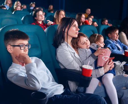 Spectators sitting in comfortable chairs and watching film in cinema. Boy looking with interest at screen with steadfast eyes. Little pretty girl with closed eyes sitting on her mom laps. Reklamní fotografie