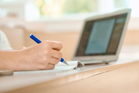 Students hand keeping a pen and writing in notebook. Working with educational scientific project. Modern laptop on background. Blue ballpen. Wooden desk.